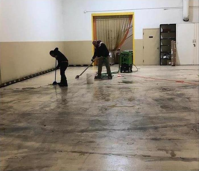 A warehouse cleared out with SERVPRO employees cleaning the floors.