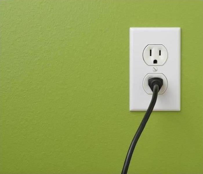 An electrical outlet on a green wall