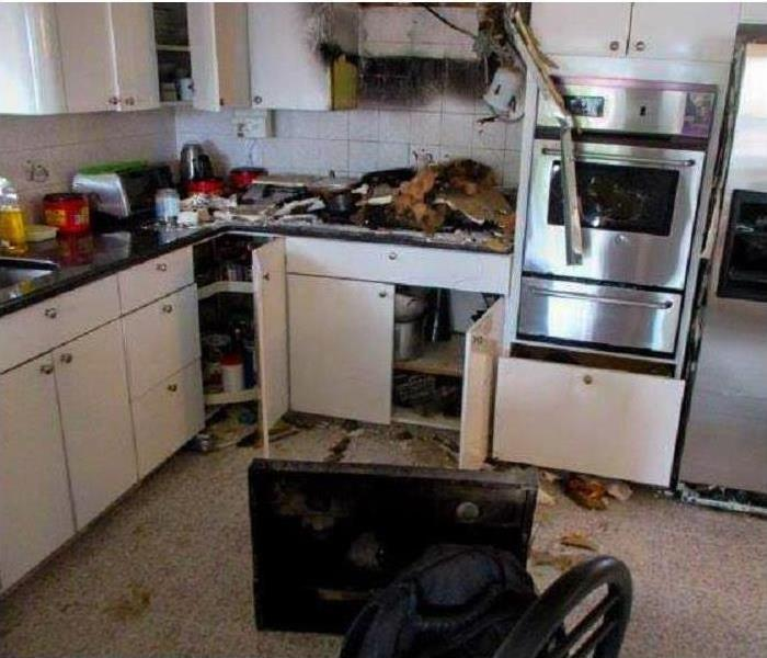A burned-out microwave in a kitchen.