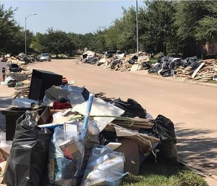 Household debris is piled in front of homes in a neighborhood
