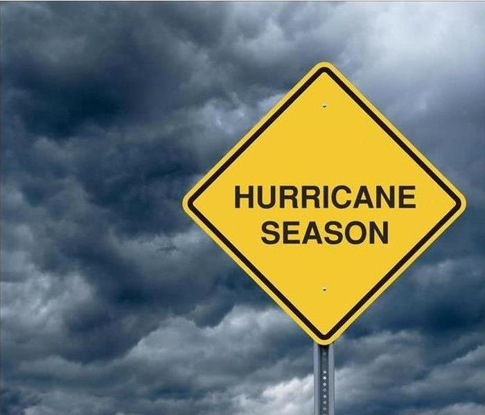 "A sign says ""Hurricane Season"" against a background image of a hurricane."